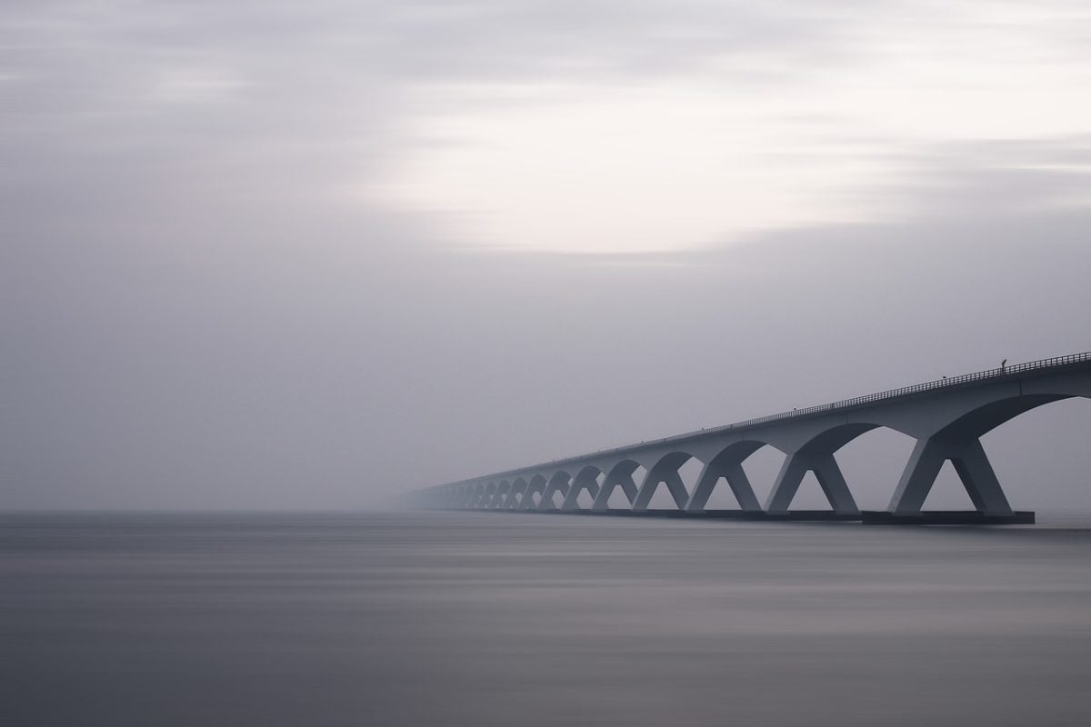 An elegant, multi-arched bridge crosses still grey-blue water below a grey sky with a light patch withe more light