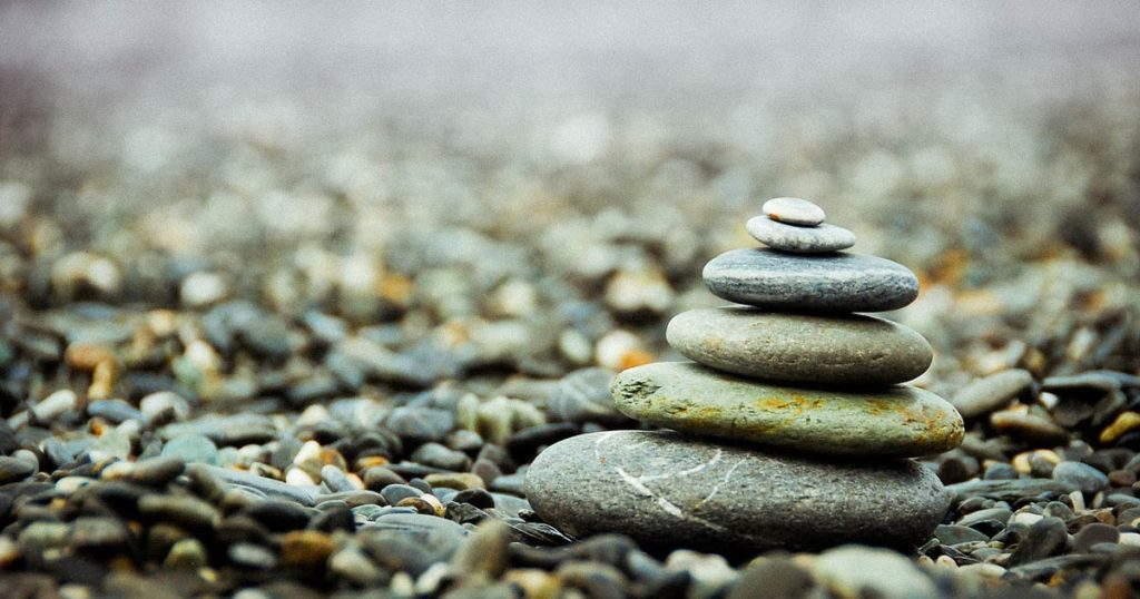 A small stack of stones on a pebble beach rest simply.