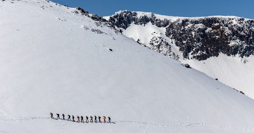 A line up of people walking on a snow covered mountain with a rocky mountain top and blue clear sky behind them.