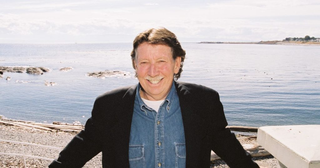 Bruce Elkin grinning on the beach at Ross Bay, Victoria