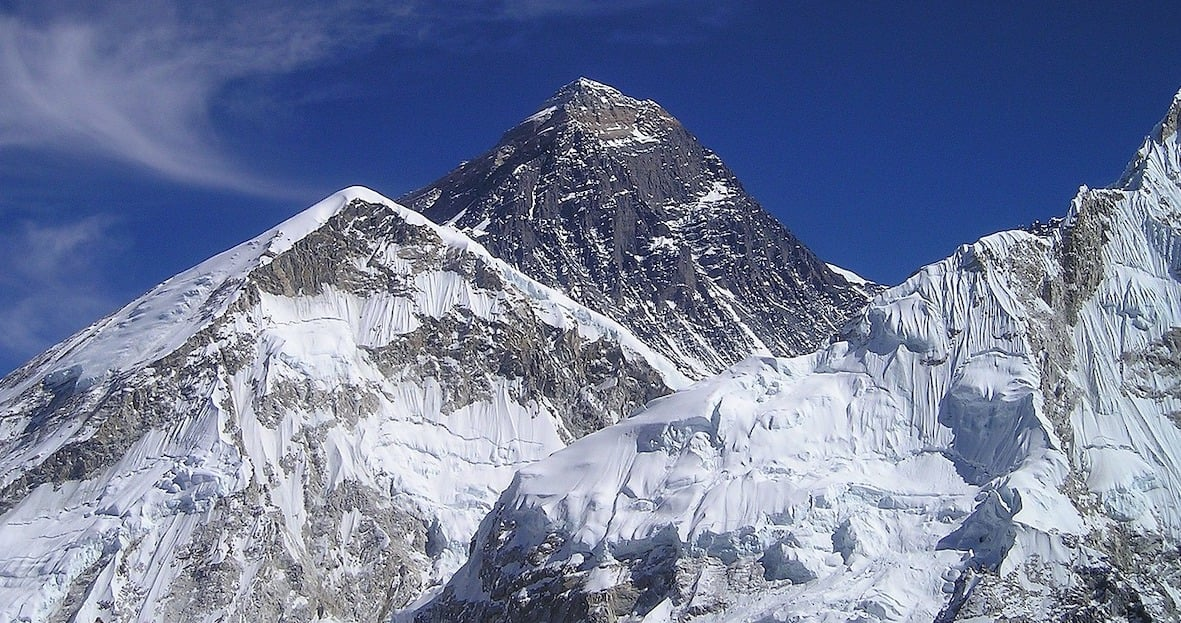 Photo of the Tibetan side of Mt Everest, with two smaller peaks in the foreground. Much snow and ice on the peaks and a trail of spindrift blowing off one them. Deep blue sky backing it all.