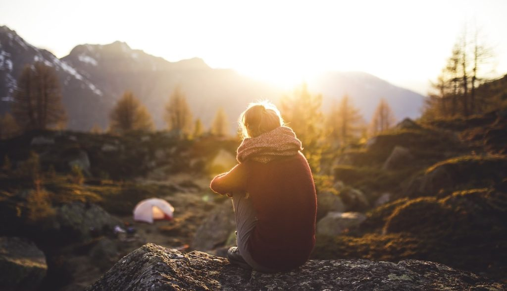 Teen girl sits alone in rocks above her mountain camp, pondering her life purpose. Sun setting behind peaks. Her tent visible below.