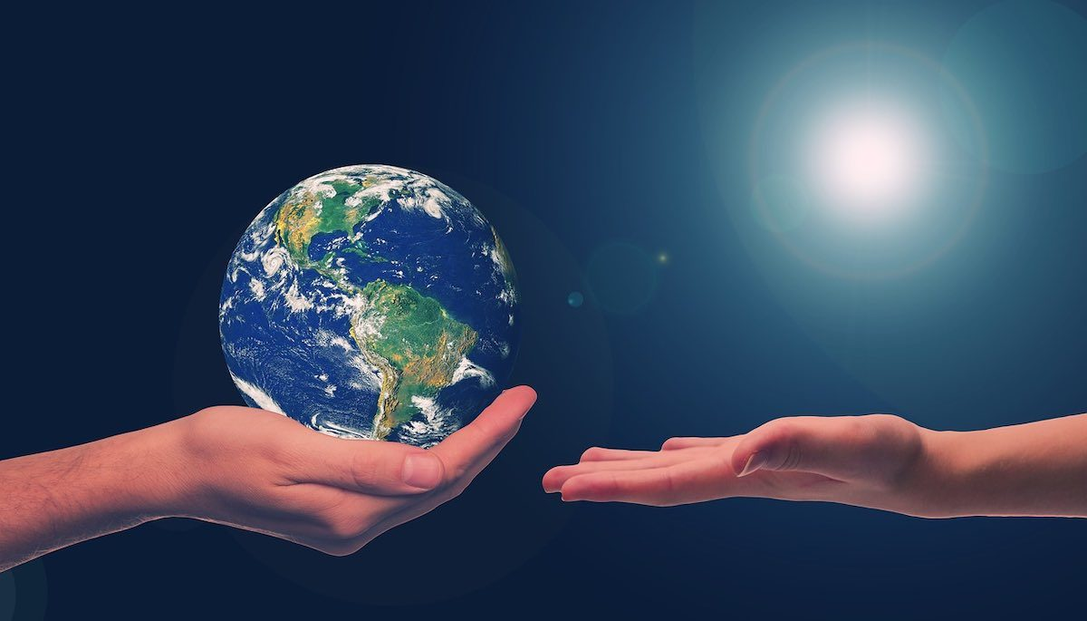 A hand cups an image of Earth from pace and appears to be handing it to smaller hand. Blue space background with sunlight in upper right corner.