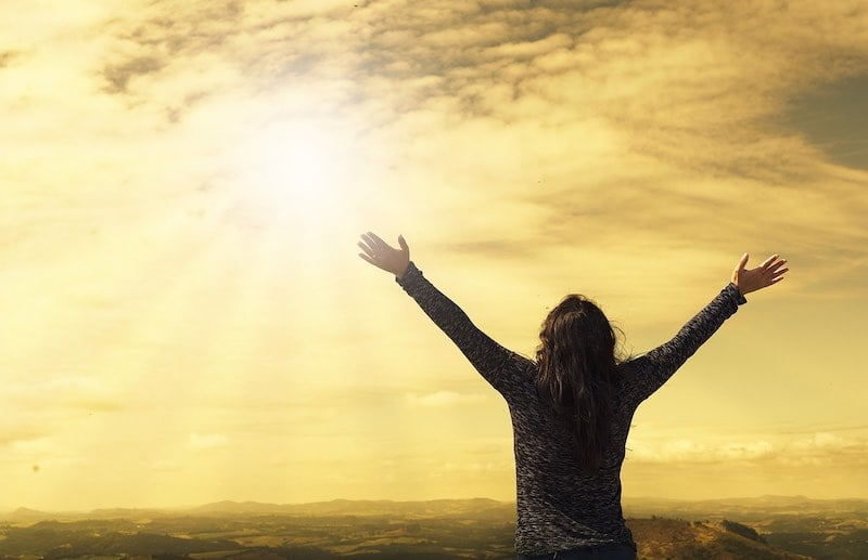 Woman with arms outspread above her shoulders is standing on the edge of the ocean, looking at rays of sun bursting through the clouds.