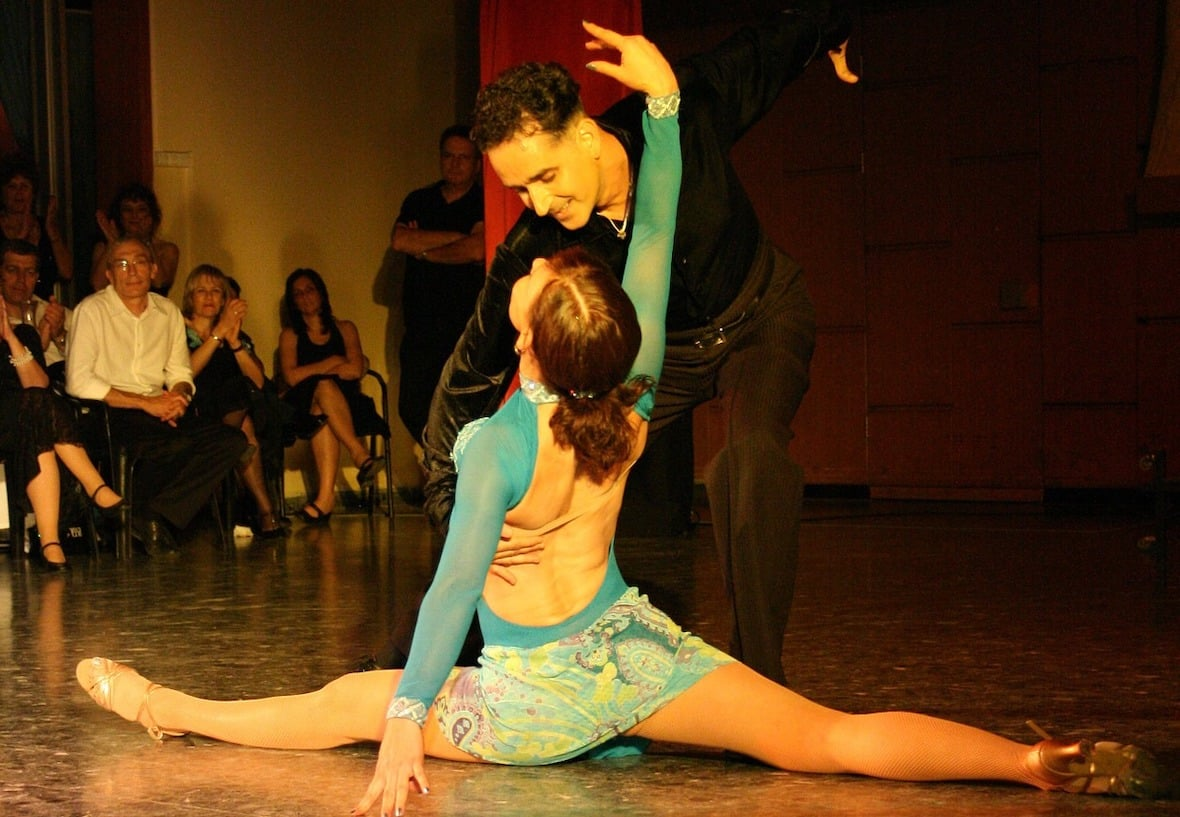 Tango dancers demonstrating technique to burn. A woman in a beige and aqua body suit and a short skirt is doing the splits, while her partner, in black pants and shirt, has his hand on her waist, ready to lift her up.