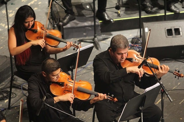 "Close up of three violinists playing in an orchestra, illustrating the importance of practicing until  you have ""technique to burn."""