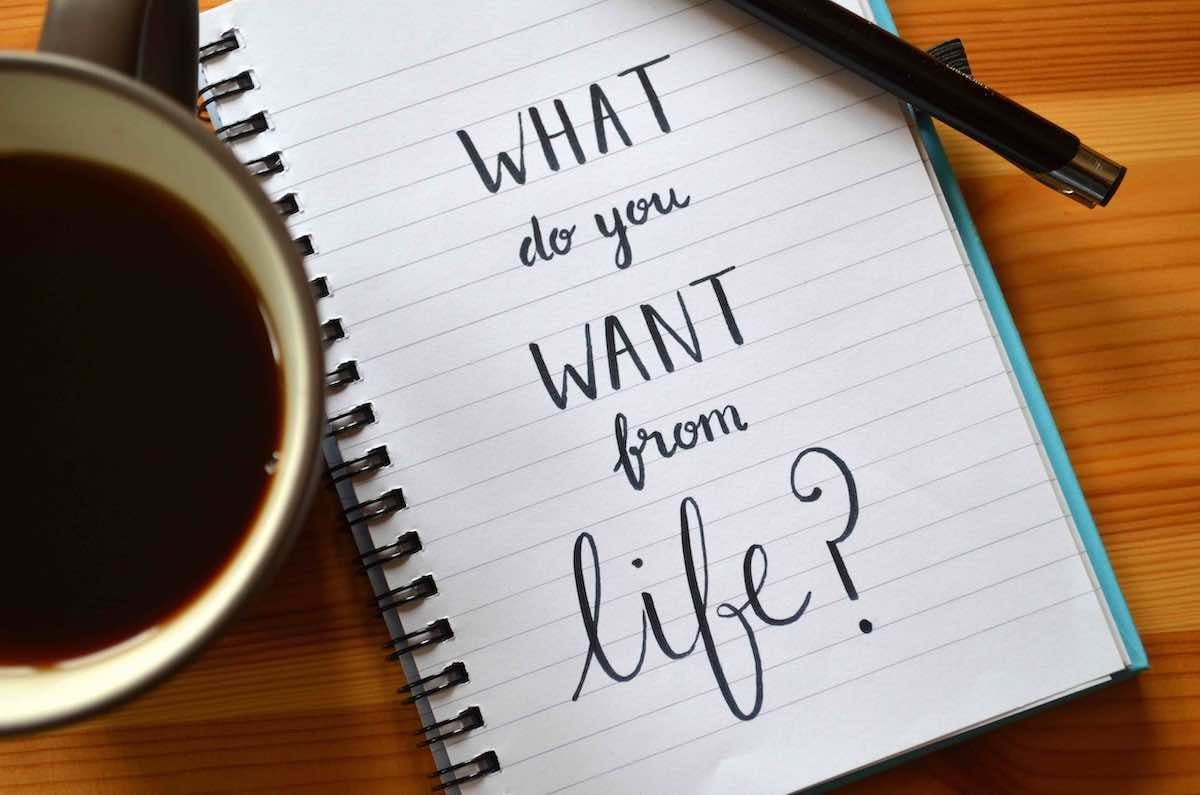 "A lined, spiral-bound notebook sits open on a wooden table between a cup of black coffee and a pen. The notebook is lined and in large letters the words ""What do you want from life"" cover most of the page."