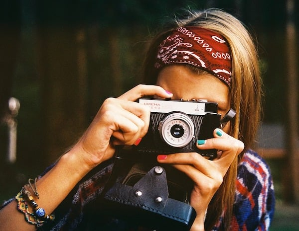 A blondwoman in a striped, multi-coloured shirt, wearing a red, paisley headband and hippy beads on one wrist holds a small, older single lens reflex camera to her left eye. Her pointing finger on her right hand is pushing the shoot button on the camera.