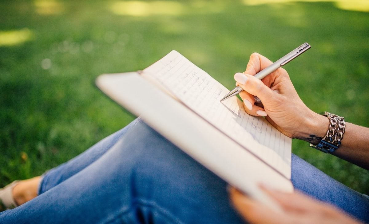 A woman sits in a grassy meadow wearing blue jeans and writing in a journal propped on her knees.