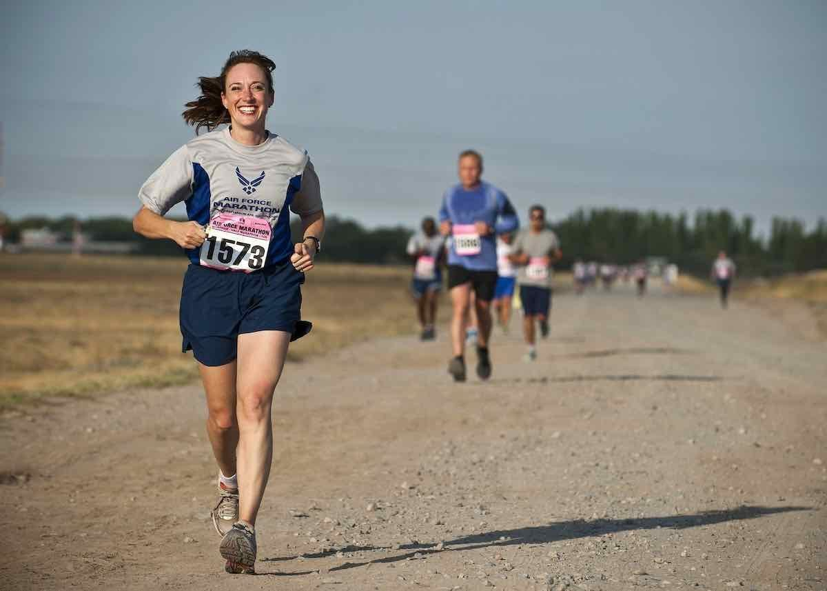 A grinning woman in navy blue shorts and navy and grey t-shirt with the number 1573 pinned to it is running a lightly-gravelled road, in front of  a man in a light blue t-shirt and black shorts, and indistinguishable other runners. The woman's dark hair is blowing to one side, and she looks very happy.