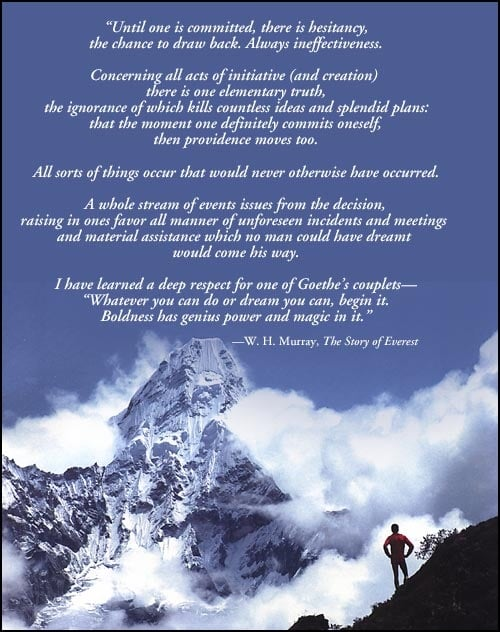 The Himalayan, snow and ice covered massif of Ama Dablam dominates the frame. Clouds swirl around its ridges, with blue sky behind. In the bottom right corner a silouetted man with hands on hips stands on a nearby ridge, looking out at the spectacular peak.