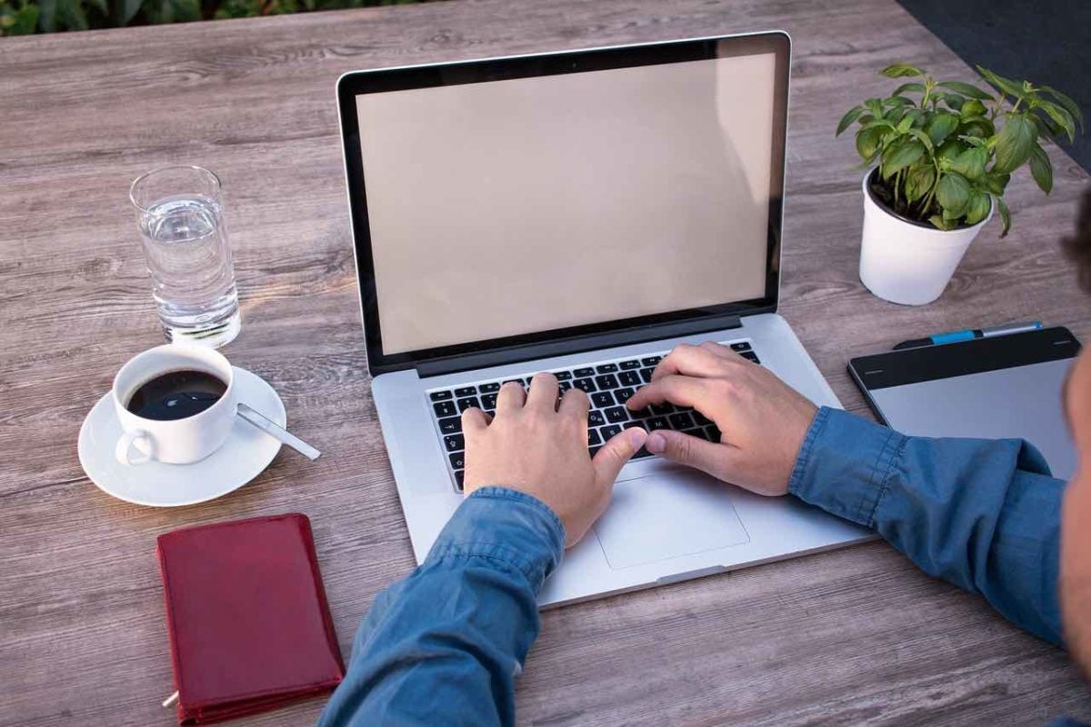On grey wooden desk, a laptop is surrounded by a phone, a cup of coffee, a glass of water, a plant, a notebook and a phone. The writer's arms and hands can be seen typing. As can the blue sleeves of the writer's shirt