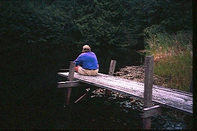 Man sits on the end of a rustic dock, above a dark pond, surrounded by heavy foliage. He wears a beige ball cap, a blue pullover and kaki shorts.