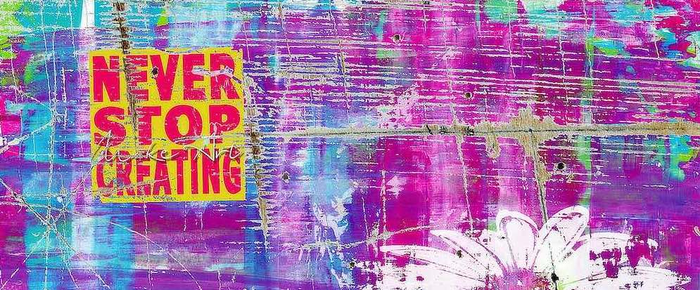 """A rough looking graphic, with the words """"Never Stop Creating,"""" one under the other, are written in red, in a yellow box, on the top left corner of a grungy multicoloured wall. A large white daisy, sketch lines visible pokes up from the bottom right"""