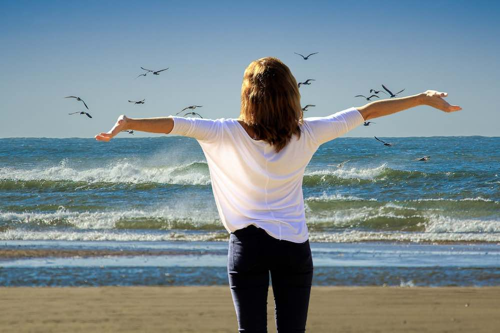 A woman in black pant and billowy, white blouse, stands on the seashore, arms outspread, head uplifted, watching the small breakers roll  in. Evokes, openness, relaxation, energy.
