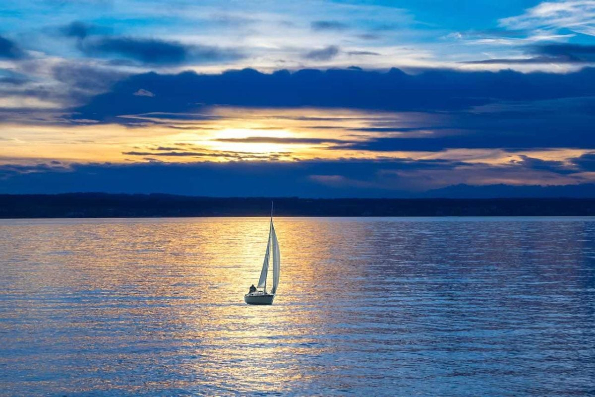 """Sail boat with sails up, silhouetted  against an orangey-gold strip of sunshine reflected off bands of dark-grey purplish clouds. Evokes a feeling of """"heading out."""""""
