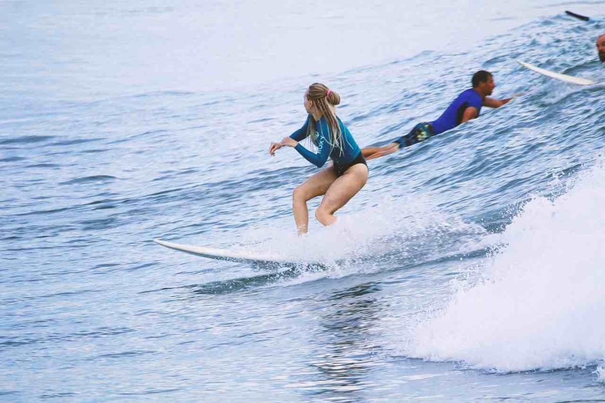 Long haired brunette woman riding a small wave. She's wearing a blue, shorty wet suit. Behind here, a man paddles out to the next week