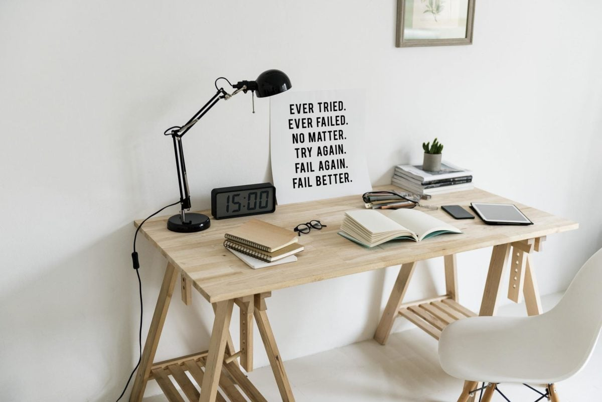 A simple, well-designed workspace. Blonde wood desk. Black elbow lamp. Clock radio with large numbers. A stack of manuals on one side at the back. At the front, left to right, a stack of wire-bounded notebooks, an open sketch book in the middle, and a phone and tablet on the right. A white plastic chair sits in front of the desk.