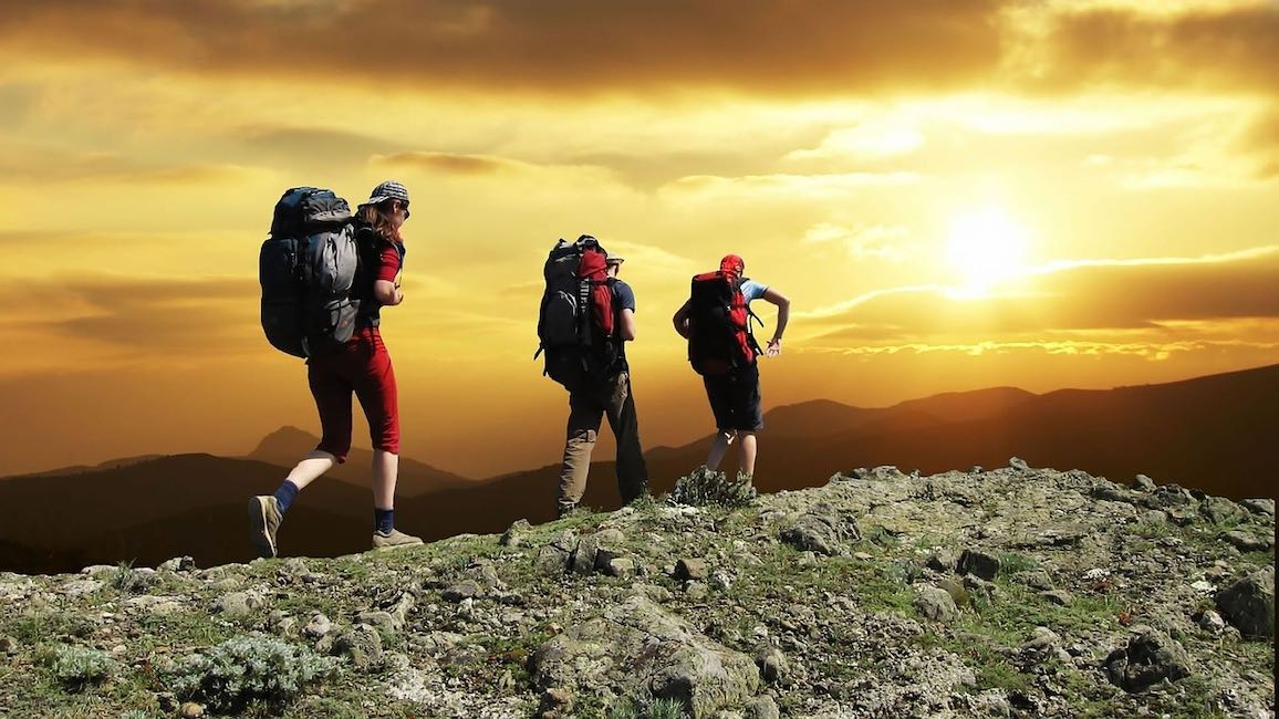 Three backpacking hikers on a rocky mountain ridge. Behind them, the sun is setting over higher mountains, and clouds through which the sun is a fuzzy yellow-white patch