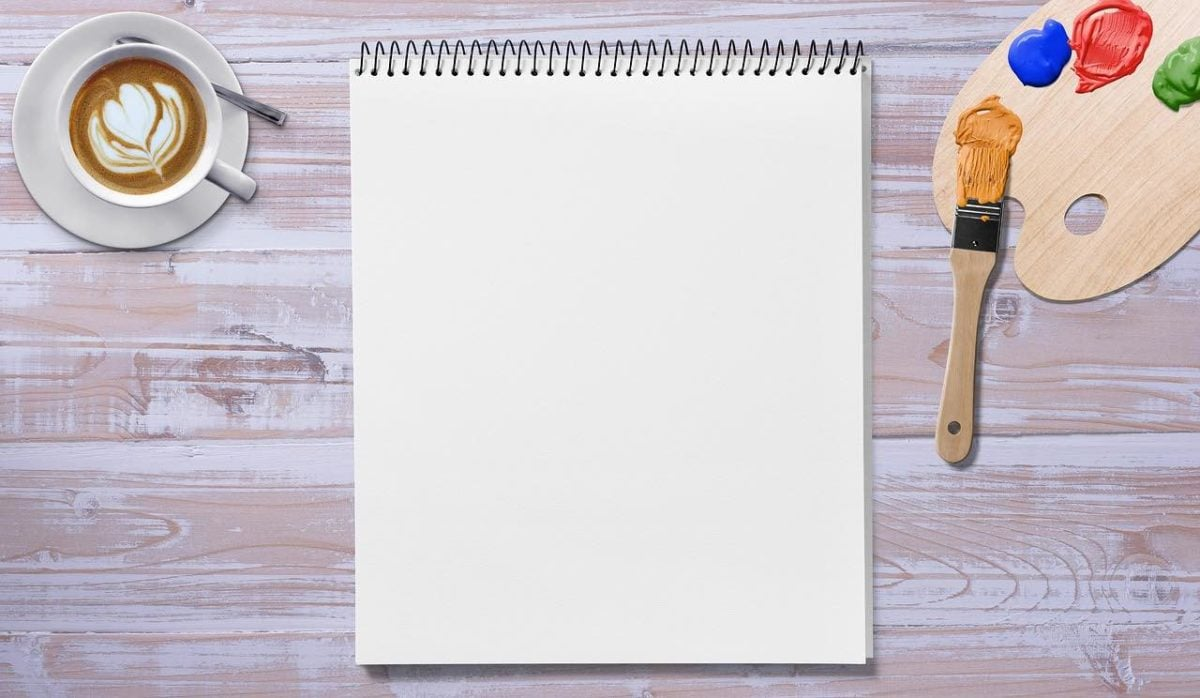 A pad of blank paper lies on a pinkish grey tabletop. In the upper left corner  sits a latte cup with a pattern drawn in on the surface. On the left a small paint pallet with abs of blue, red and green paint,  and a brush with yellow on its bristles