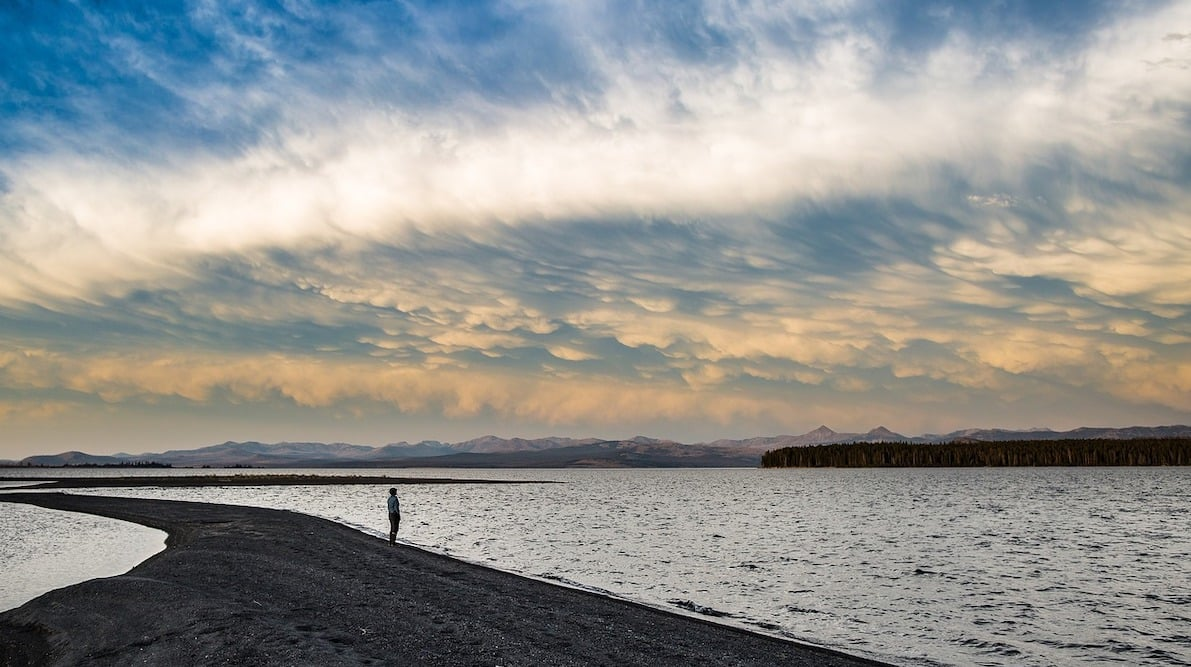 Person stands alone on a spit of land jutting out into the ocean. He's enjoying a simple moment, looking across the water to a mountain range. Overhead the multi-coloured clouds of a storm front is approaching, and eating to a sliver of blue in the upper left corner