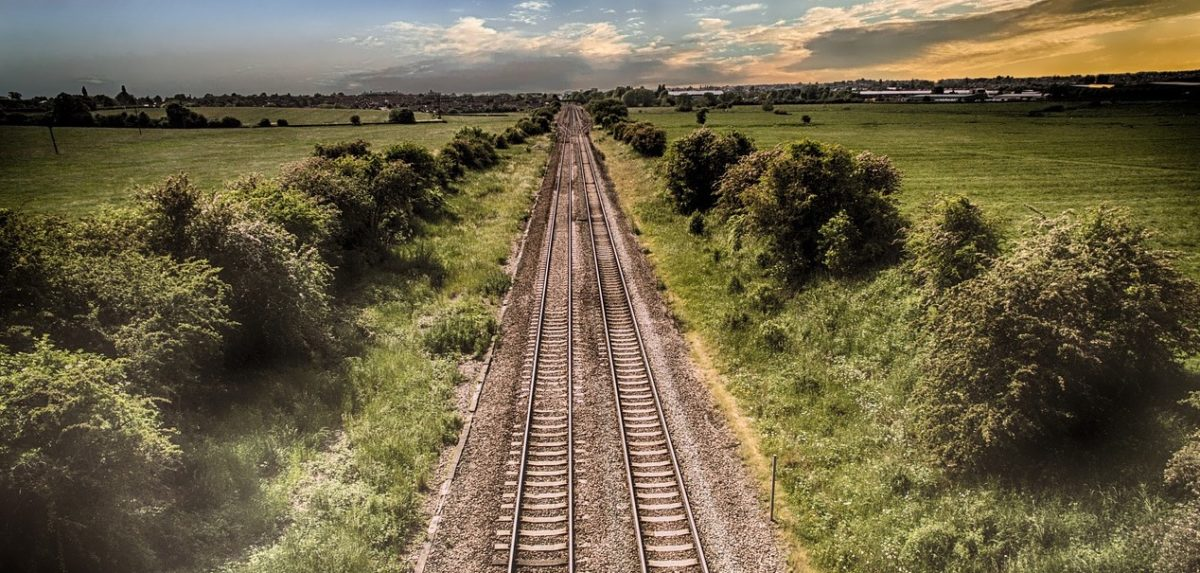 A set of double train tracks cut straight through flat farmland, flanked by hedgerows of leafy trees. A strip of multi-coloured sky on the far away horizon