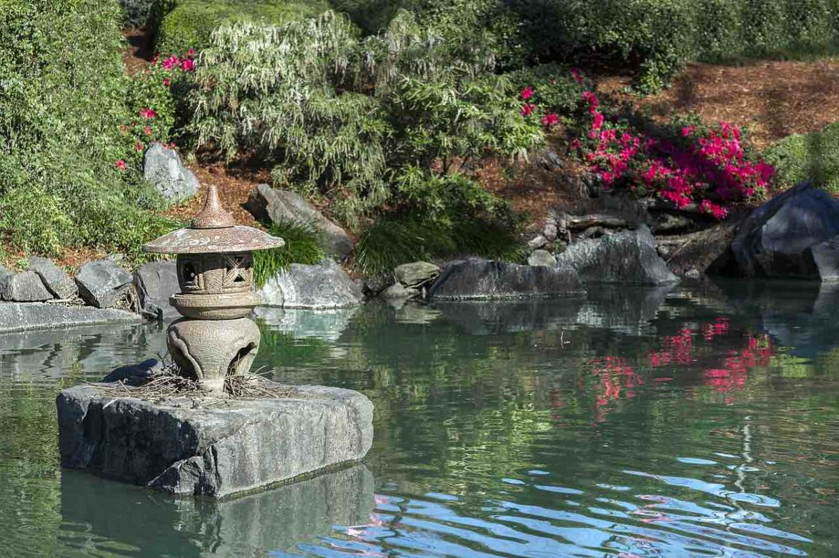A pool in a Zen garden surrounded by rocks and shrubbery. A stone lantern sits on a square, flat rock in the middle of the pool. The whole peaceful scene is an example of the simplicity on the other side of complexity